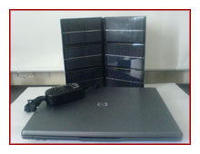 ο ηλιακός φορτιστής λάπτοπ δίπλα σε ηλεκτρονικού υπολογιστή